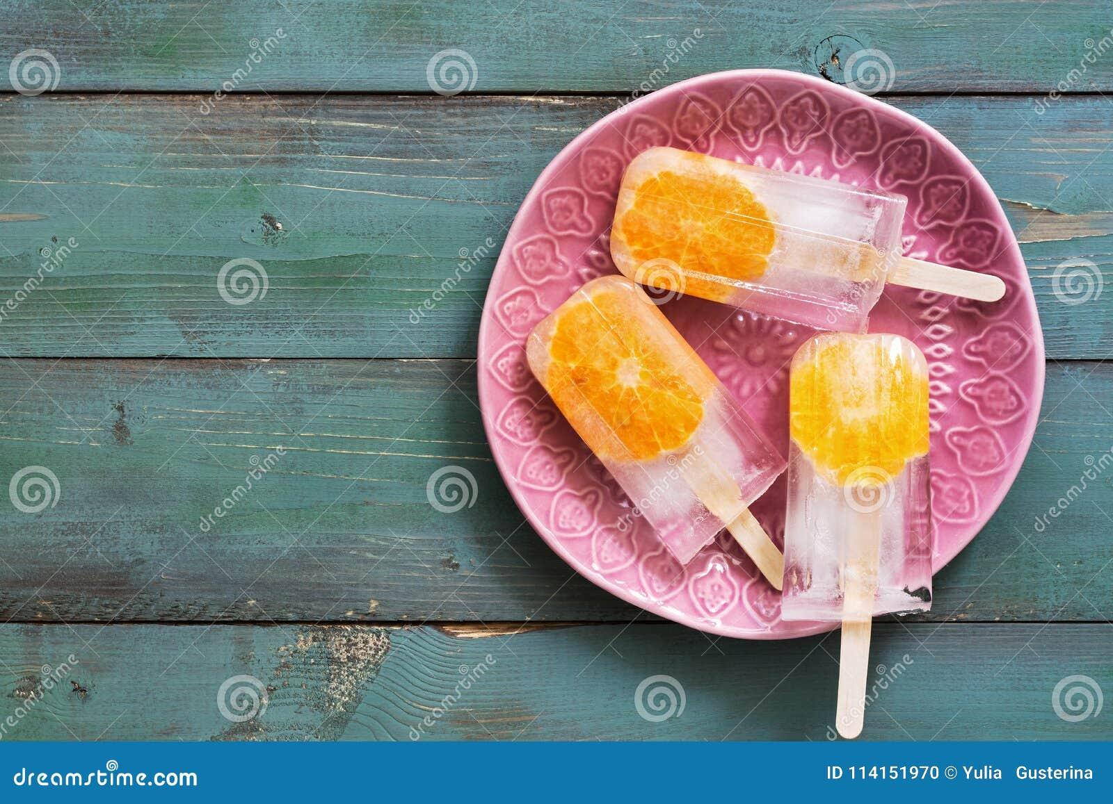 Popsicle Crème glacée fruitée avec les tranches oranges d un plat rose, fond en bois vert Dessert d été Vue supérieure, l espace