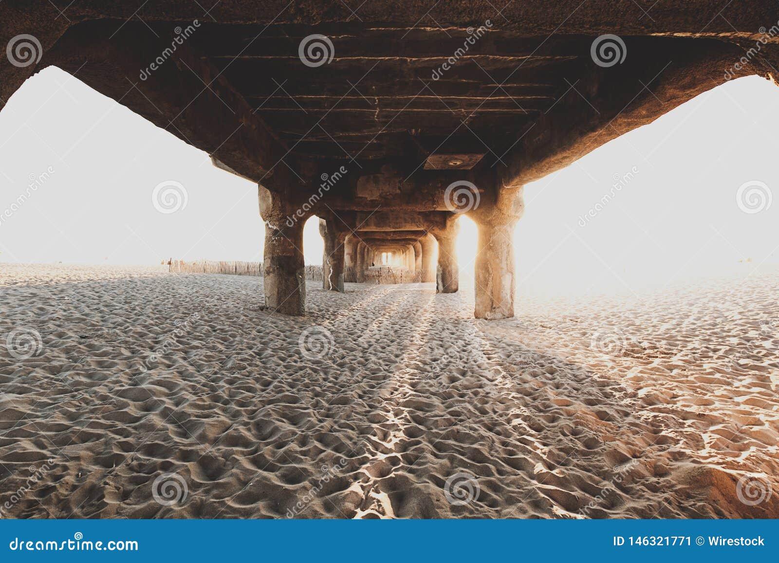 Por debajo el puente de madera en la playa arenosa