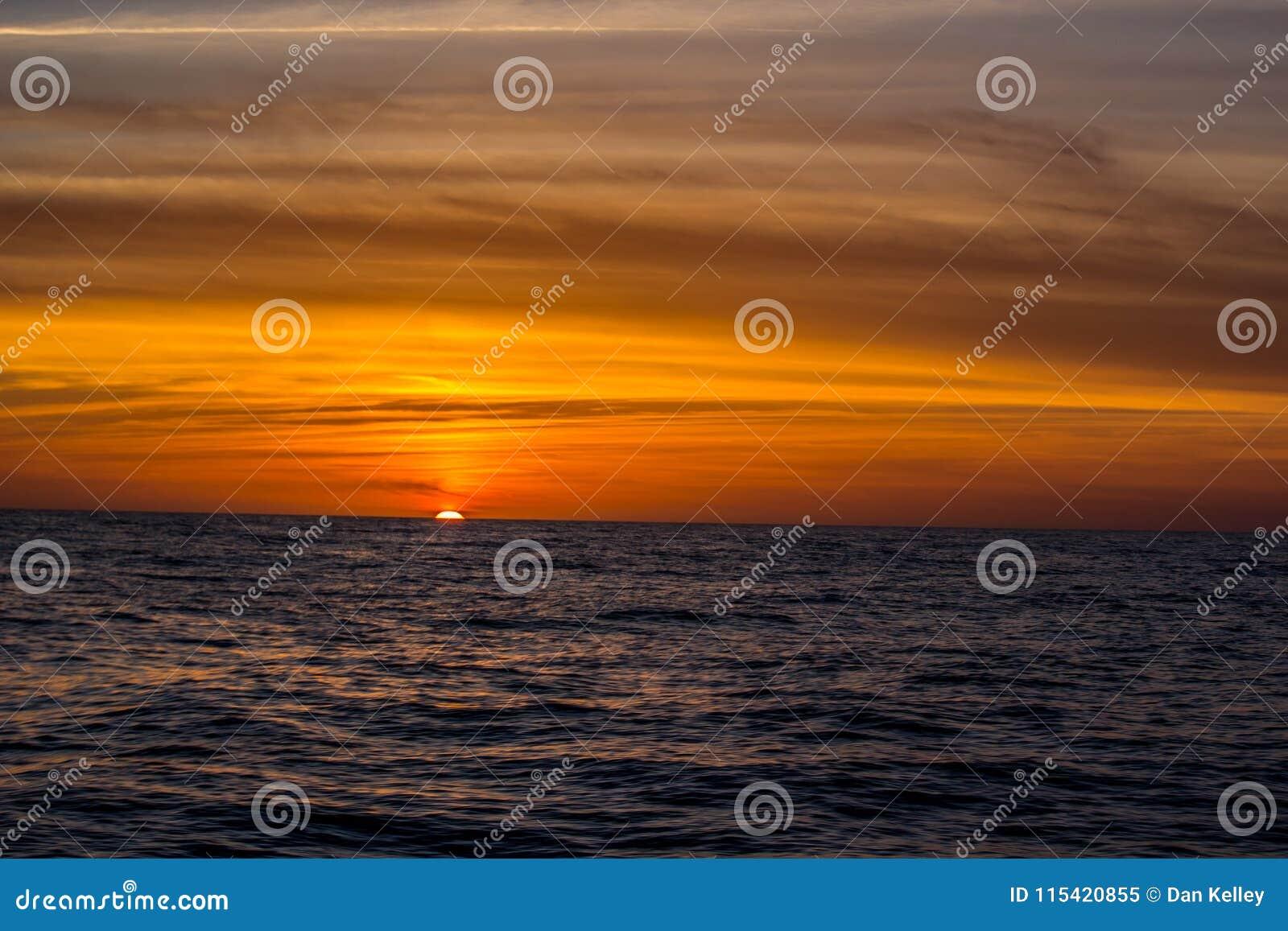 Por do sol alaranjado brilhante no Atlântico fora da costa de Florida