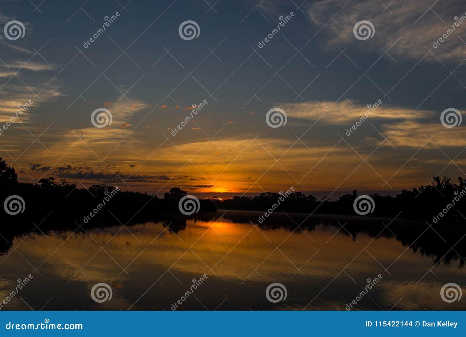 Por do sol alaranjado brilhante no Golfo do México fora da costa de Florida
