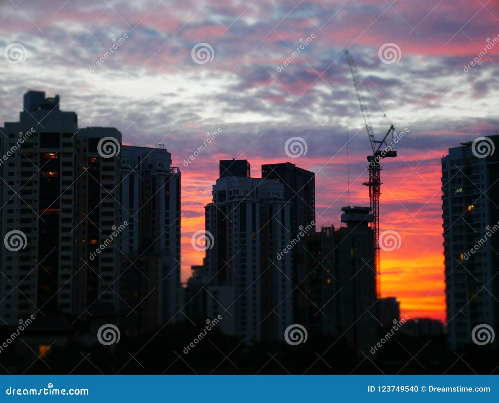 Por do sol atrás das construções com o céu nebuloso bonito