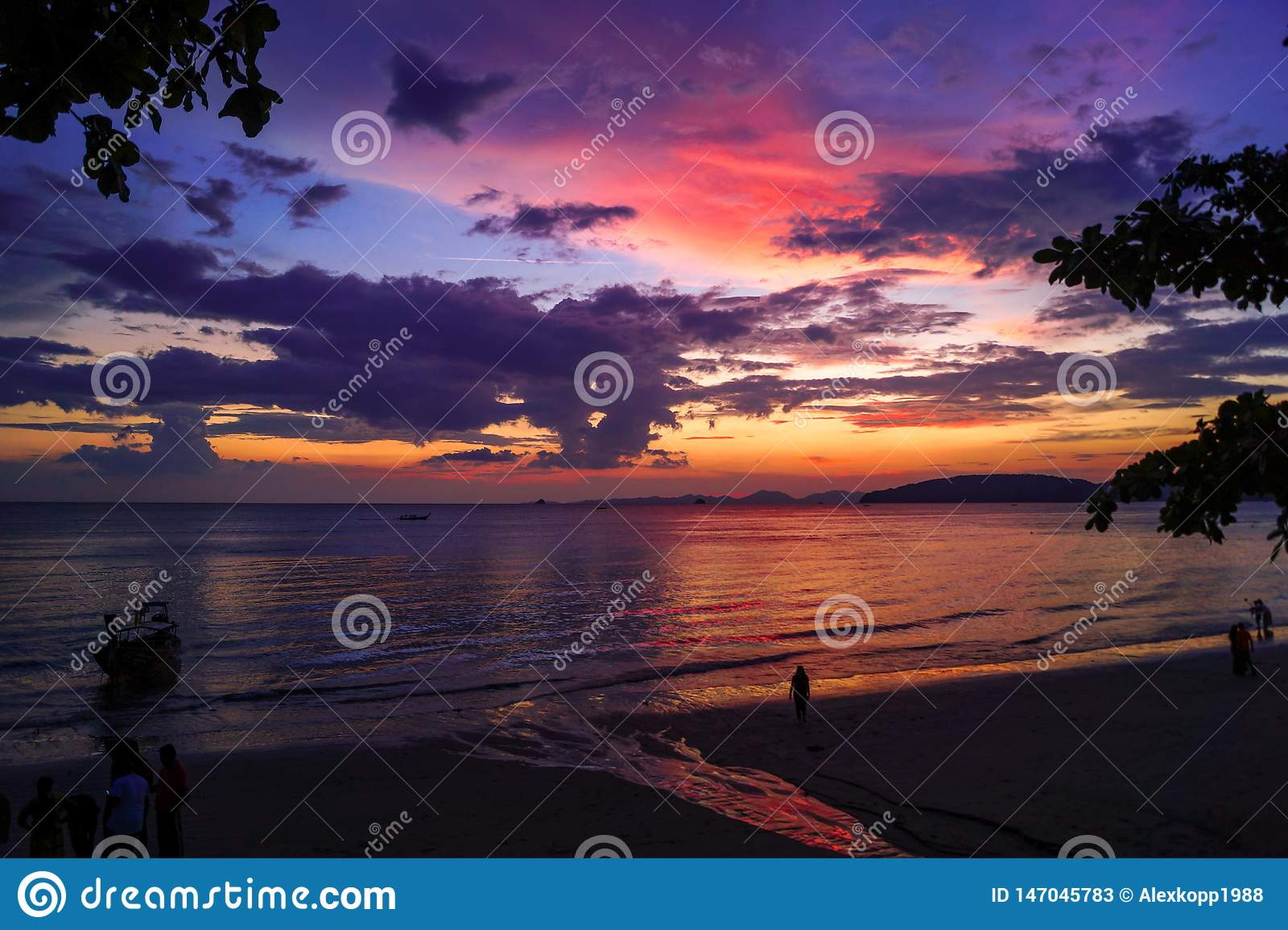 Por do sol bonito com cores vermelhas, roxas e amarelas na praia em Tailândia