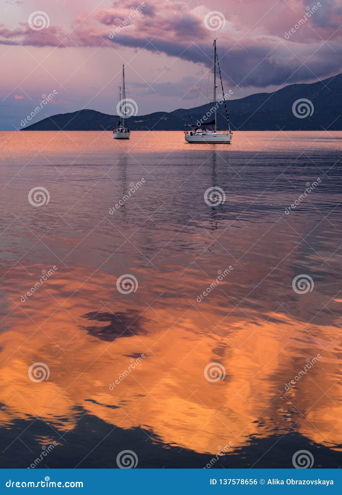 Por do sol bonito e iate no mar Ionian na ilha de Kefalonia em Grécia
