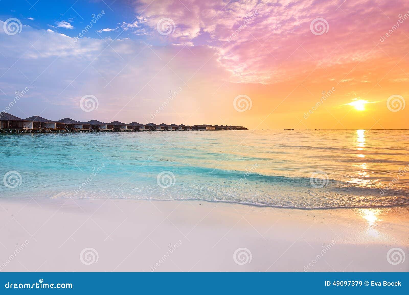 Por do sol bonito no recurso tropical com bungalows do overwater
