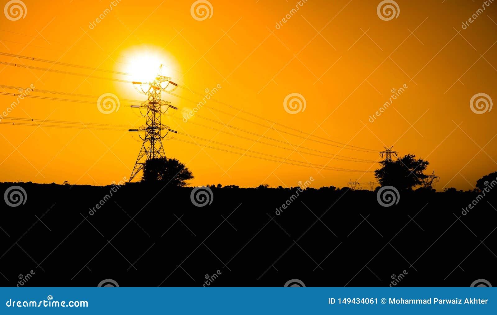 Por do sol bonito sobre a linha el?trica com os campos verdes