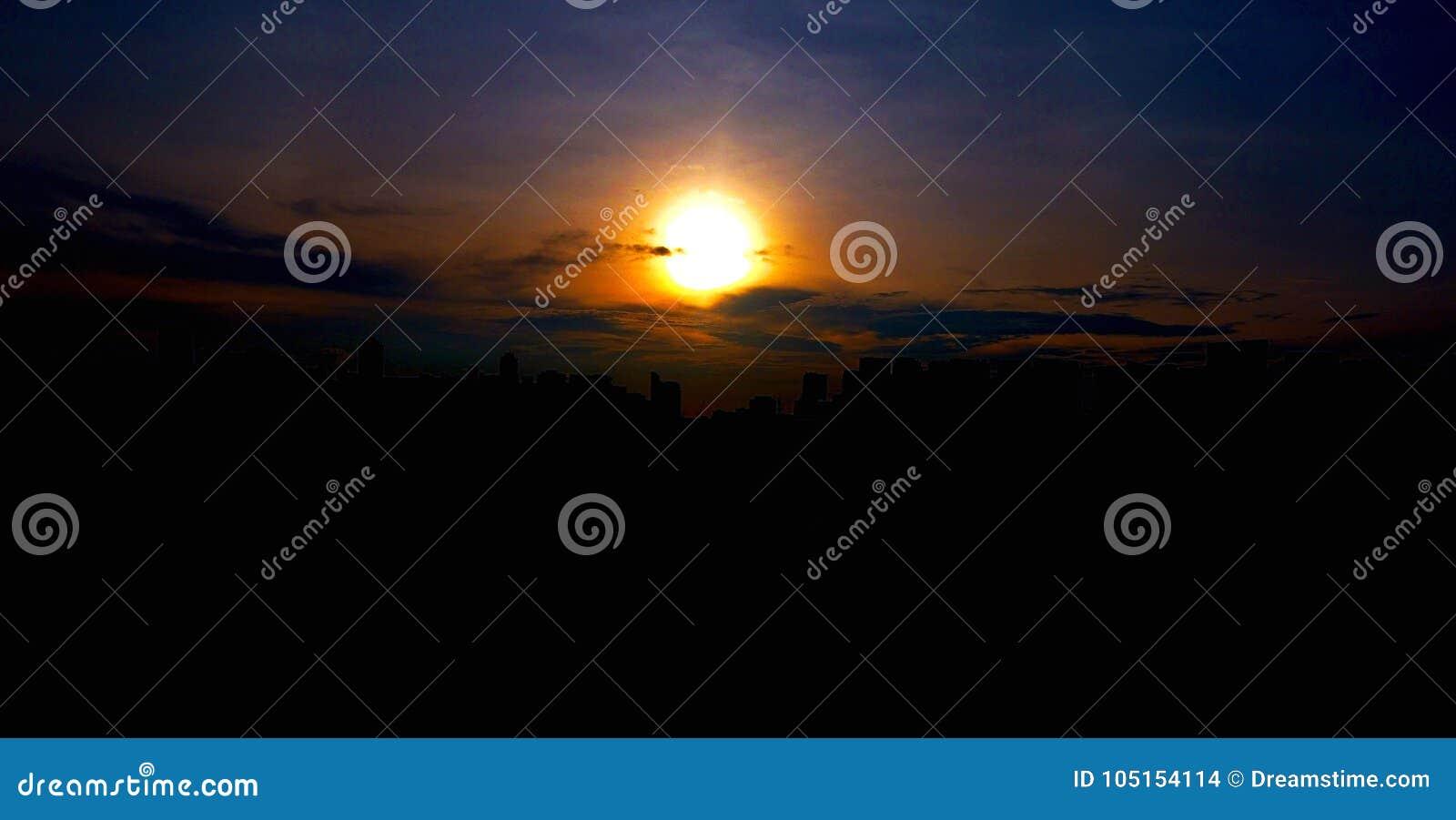 Por do sol brilhante atrás da skyline da cidade