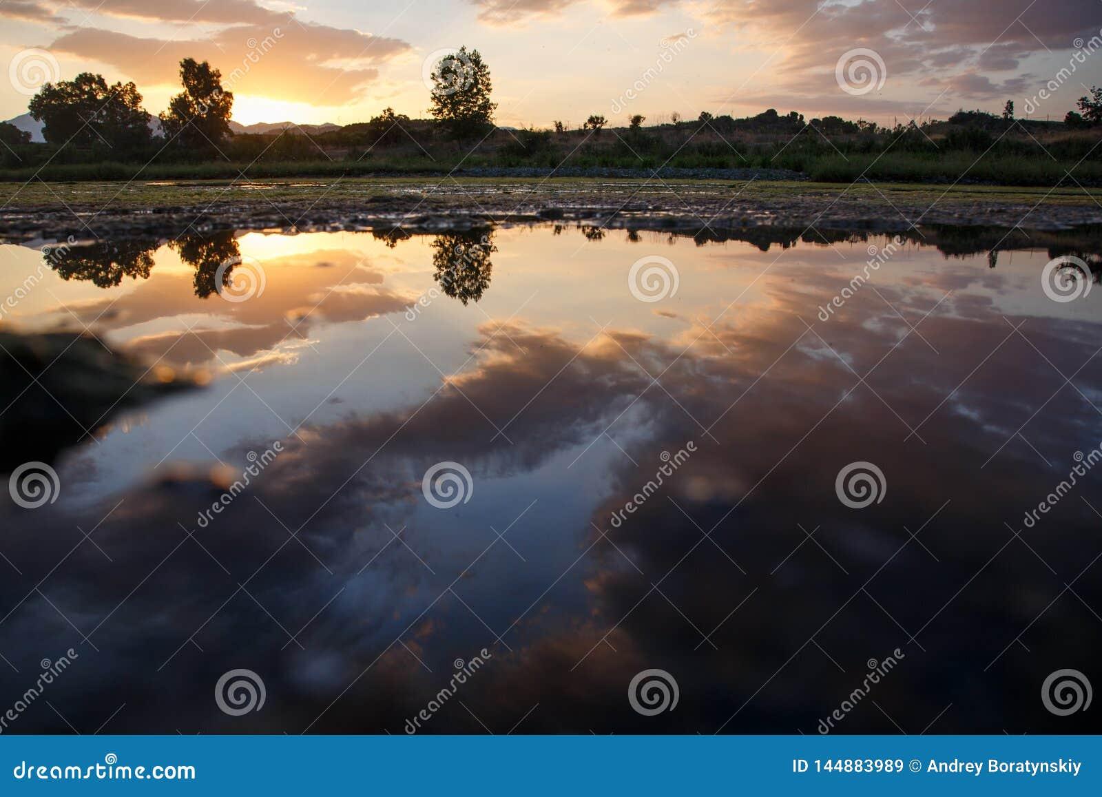 Por do sol com as nuvens refletidas na água de um lago