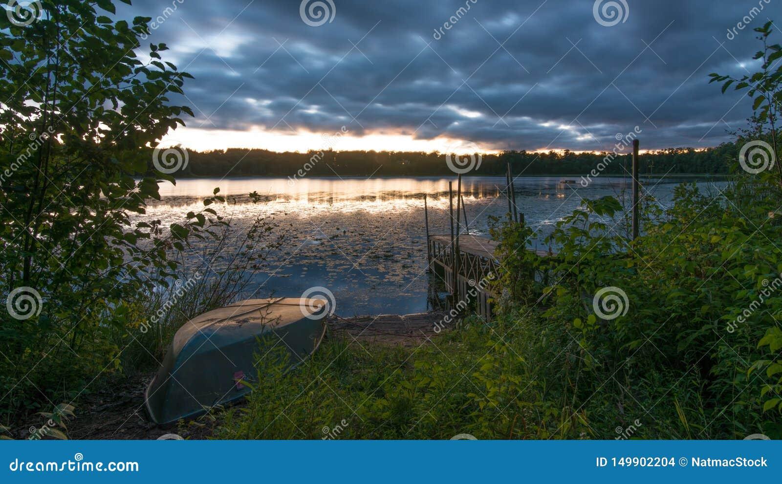 Por do sol com doca velha e o barco de fileira velho no lago remoto pequeno em Wisconsin do norte - nuvens e tempo que entram