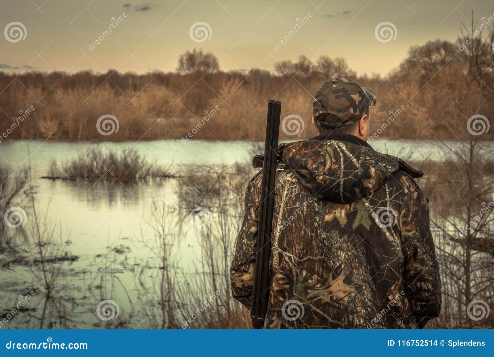Por do sol de exploração da opinião traseira da época de caça do rio da inundação da camuflagem da espingarda do homem do caçador