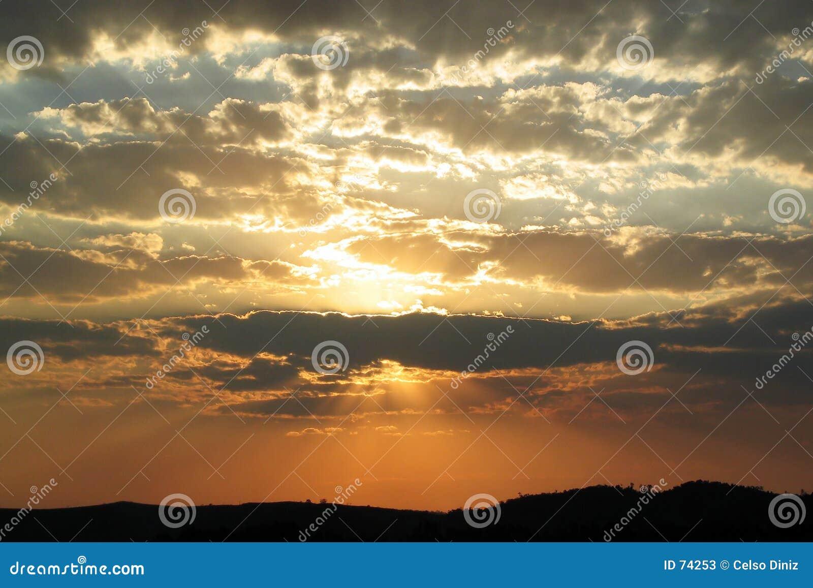 Por do sol dourado e nuvens