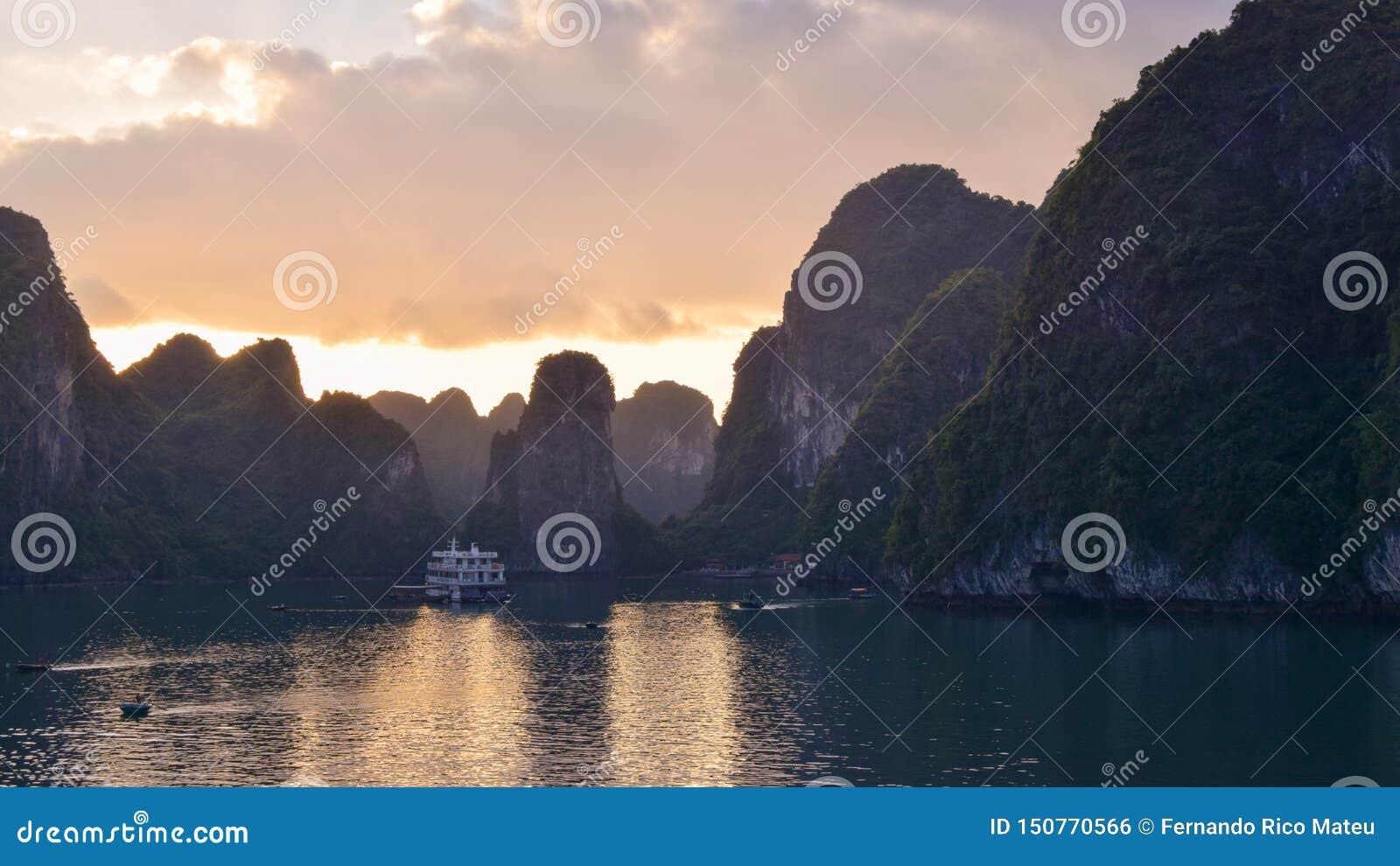 Por do sol dourado mágico na baía de Halong em Vietname, mar do Sul da China O cruzeiro navega as ilhas de madeira da rocha da na