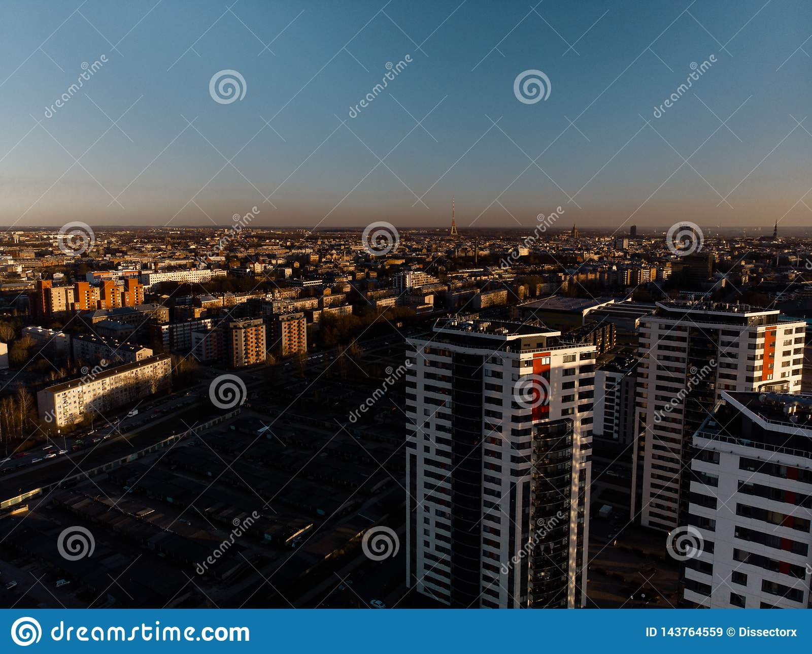 Por do sol dramático aéreo do cenário com uma vista sobre arranha-céus em Riga, Letónia - a baixa velha da cidade é visível no