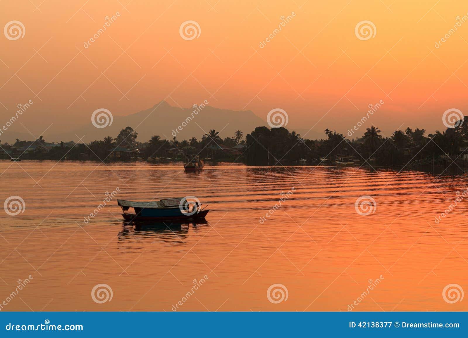 Por do sol local do barco Bornéu, Sarawak, Malásia