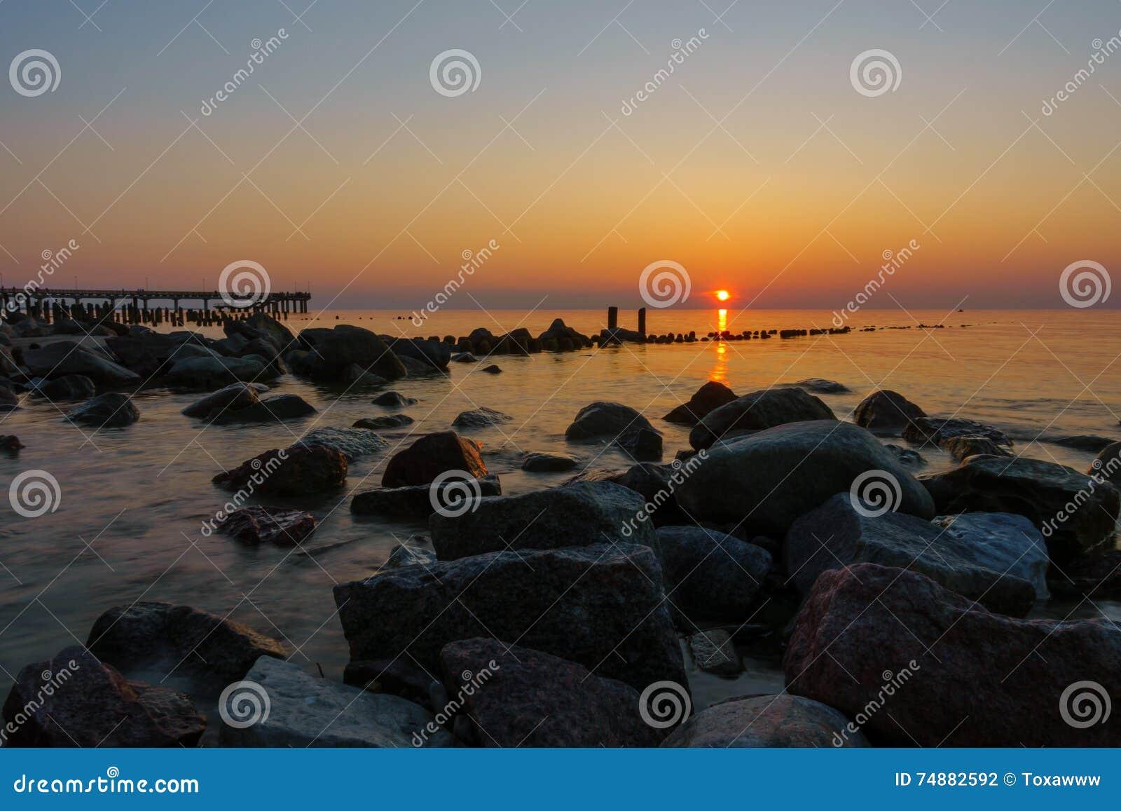 Por do sol na costa de mar Báltico