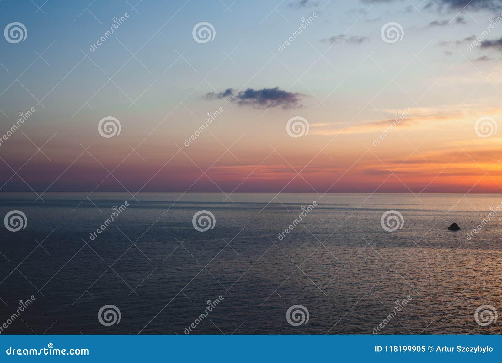 Por do sol na praia com algumas nuvens no céu Máscaras azuis e cor-de-rosa com nuvens escuras Lugar quieto Cena de relaxamento da