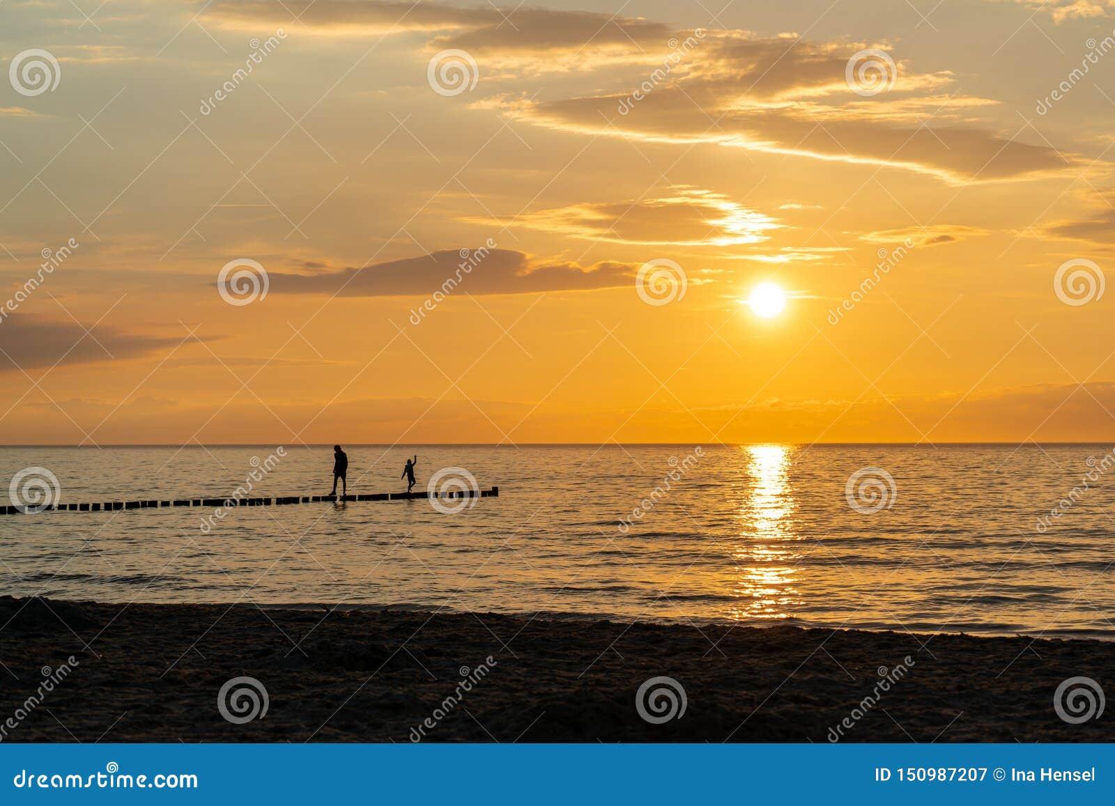Por do sol na praia com dois pessoas como silhuetas pretas no primeiro plano