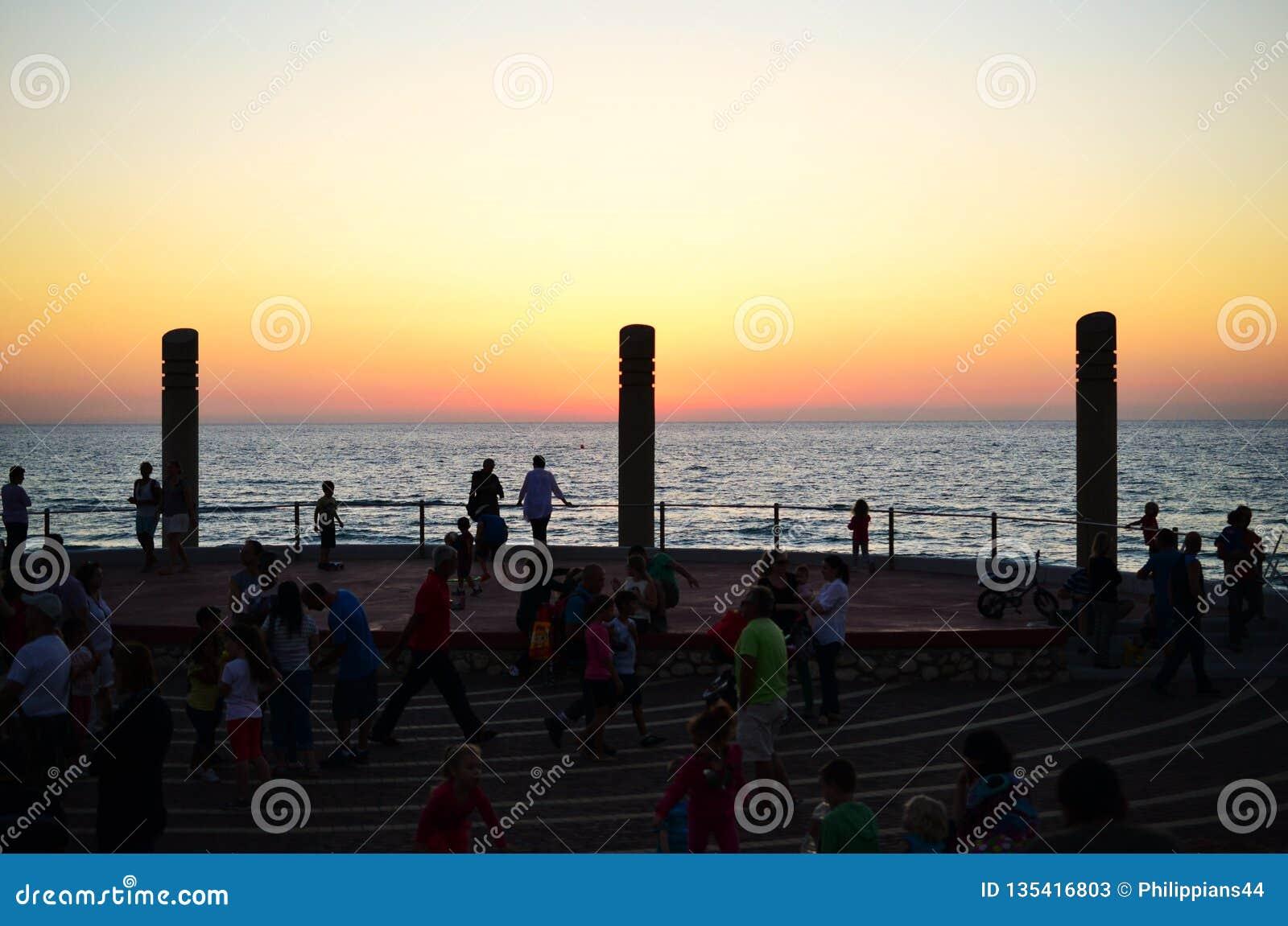 Por do sol na praia de Carmel, nos Dado de Hof, nas colunas e no quadrado, cidade de Haifa, baixa, Israel
