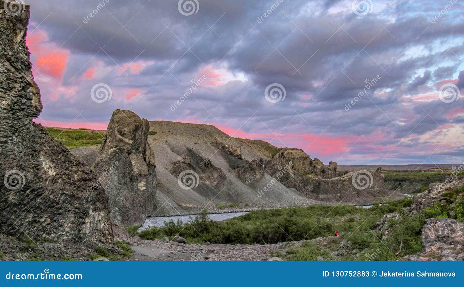 """Por do sol no †do """"†""""Asbyrgi durante o por do sol, parque nacional de Vesturdalur das formações da coluna basalto de Vatnajok"""