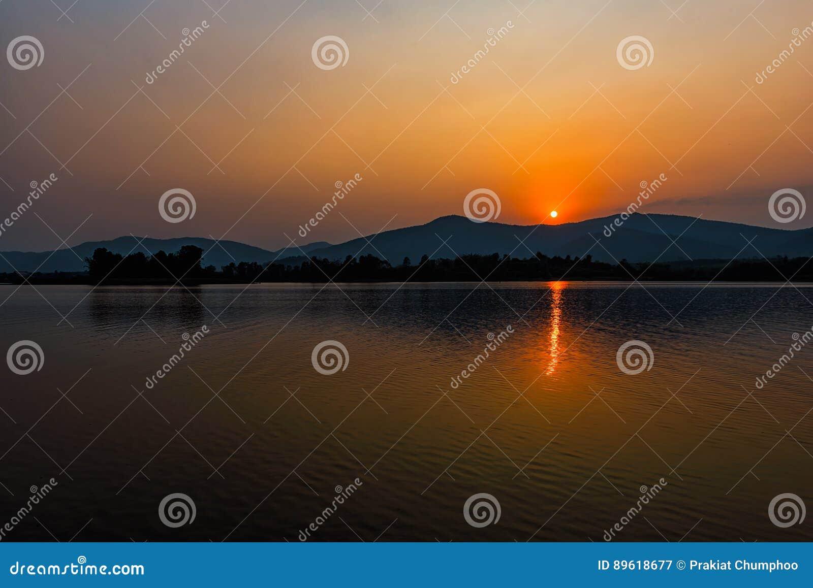 Por do sol no lago da montanha em Chiang Rai, ao norte de Tailândia