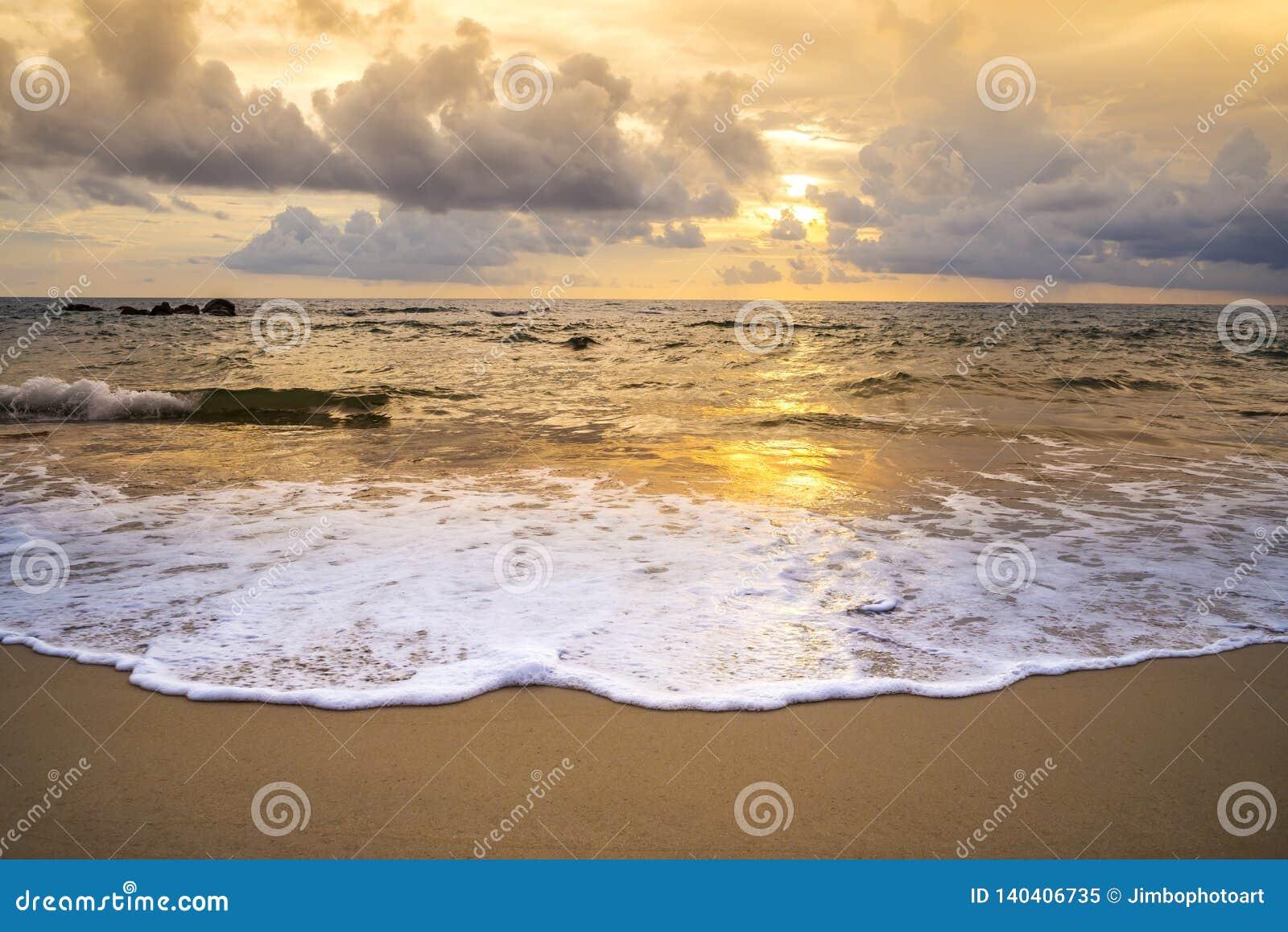 Por do sol ou nascer do sol da praia com o colorido do céu da nuvem