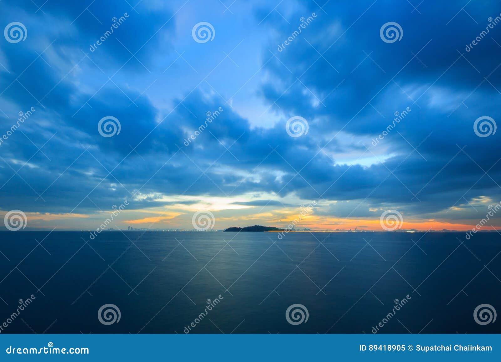 Por do sol pastel sobre o oceano em um céu nebuloso