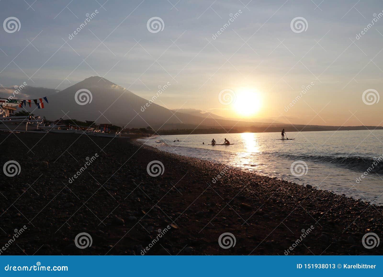 Por do sol romântico na costa de mar em Indonésia O surfista vai apreciar o paddleboard no por do sol Panorama do litoral com vul