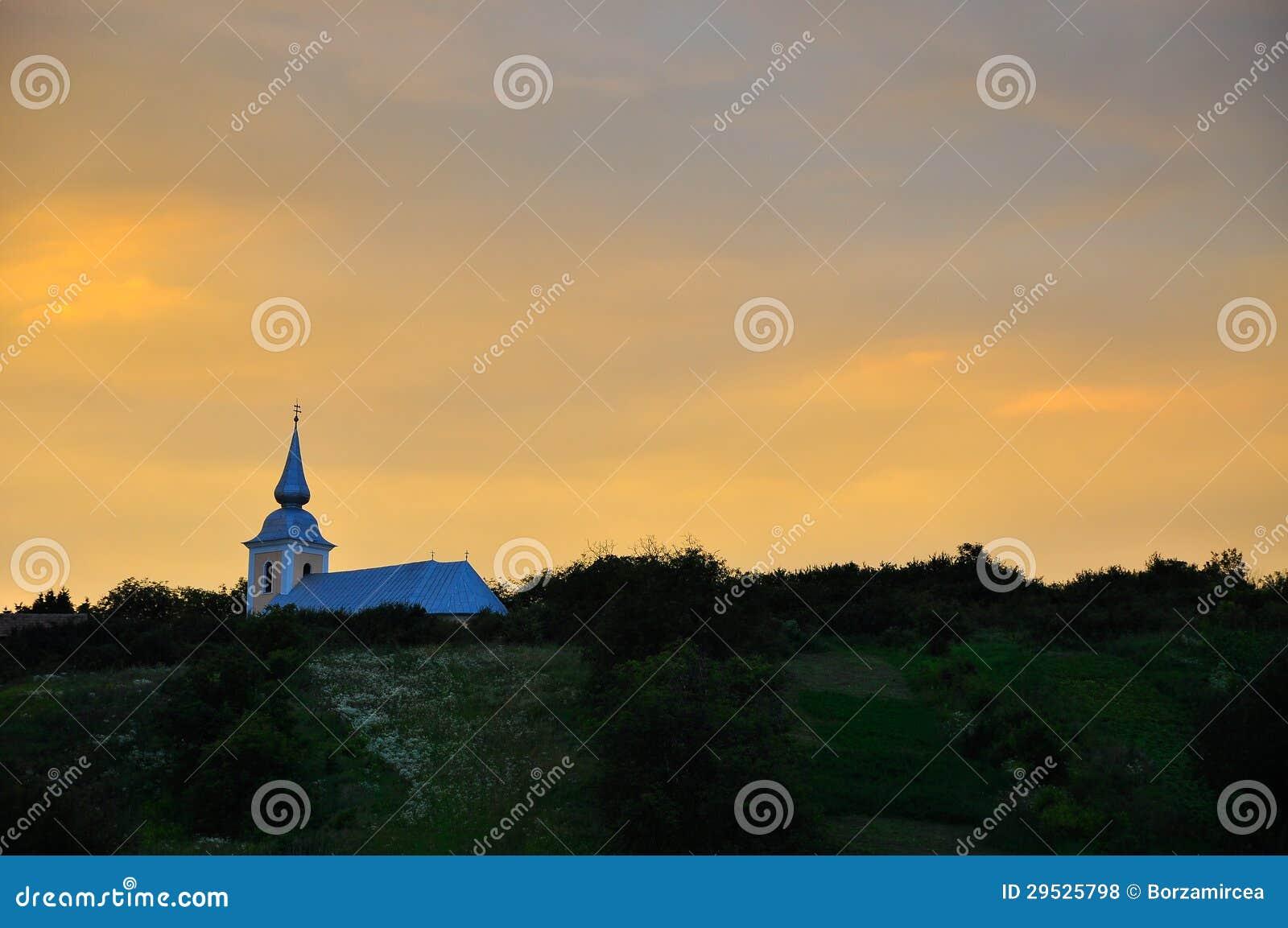 Por do sol sobre a igreja rural