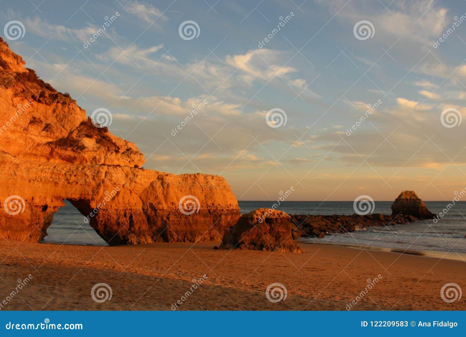Por do sol sobre penhascos na praia abandonada no Algarve, Portugal