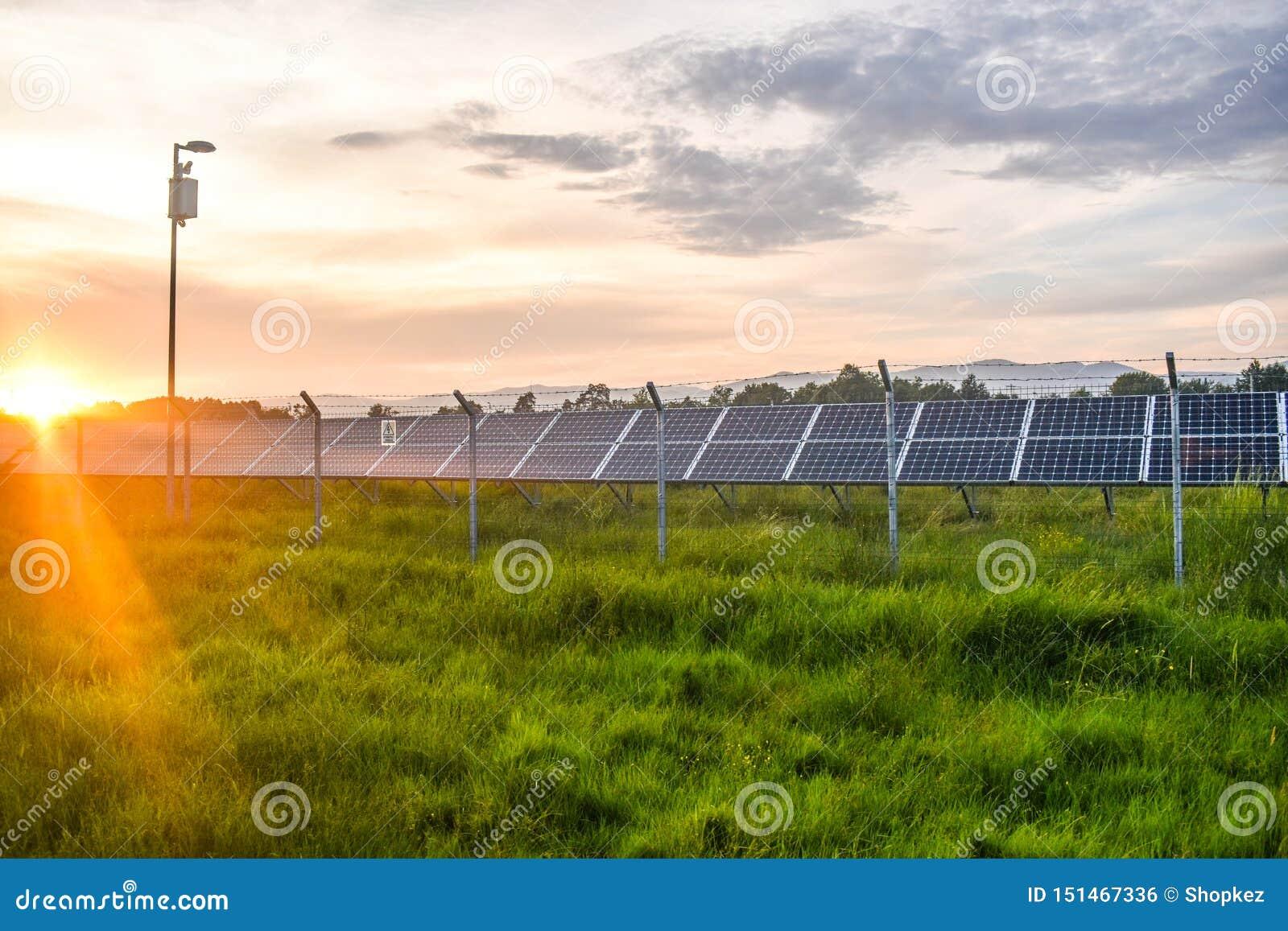 Por do sol sobre um central elétrica fotovoltaico com os módulos fotovoltaicos para a energia renovável no campo Gera??o das ener