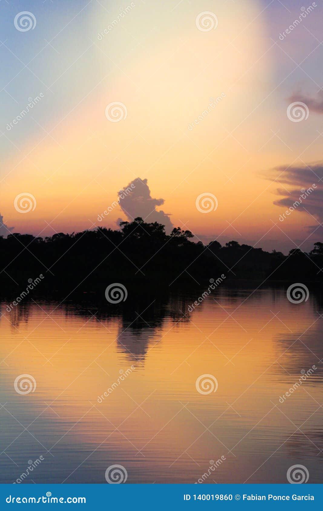 Por do sol sobre um rio com reflexões das árvores contra a luz