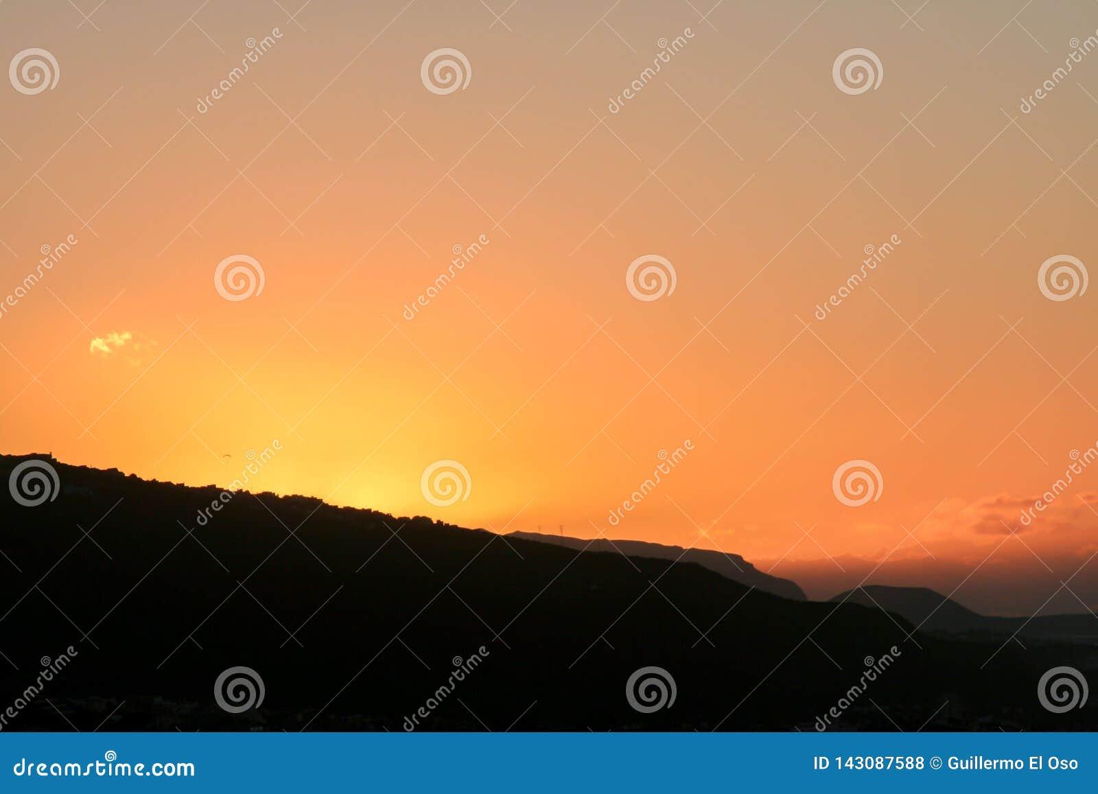 Por do sol tropical atrás das montanhas de Tenerife