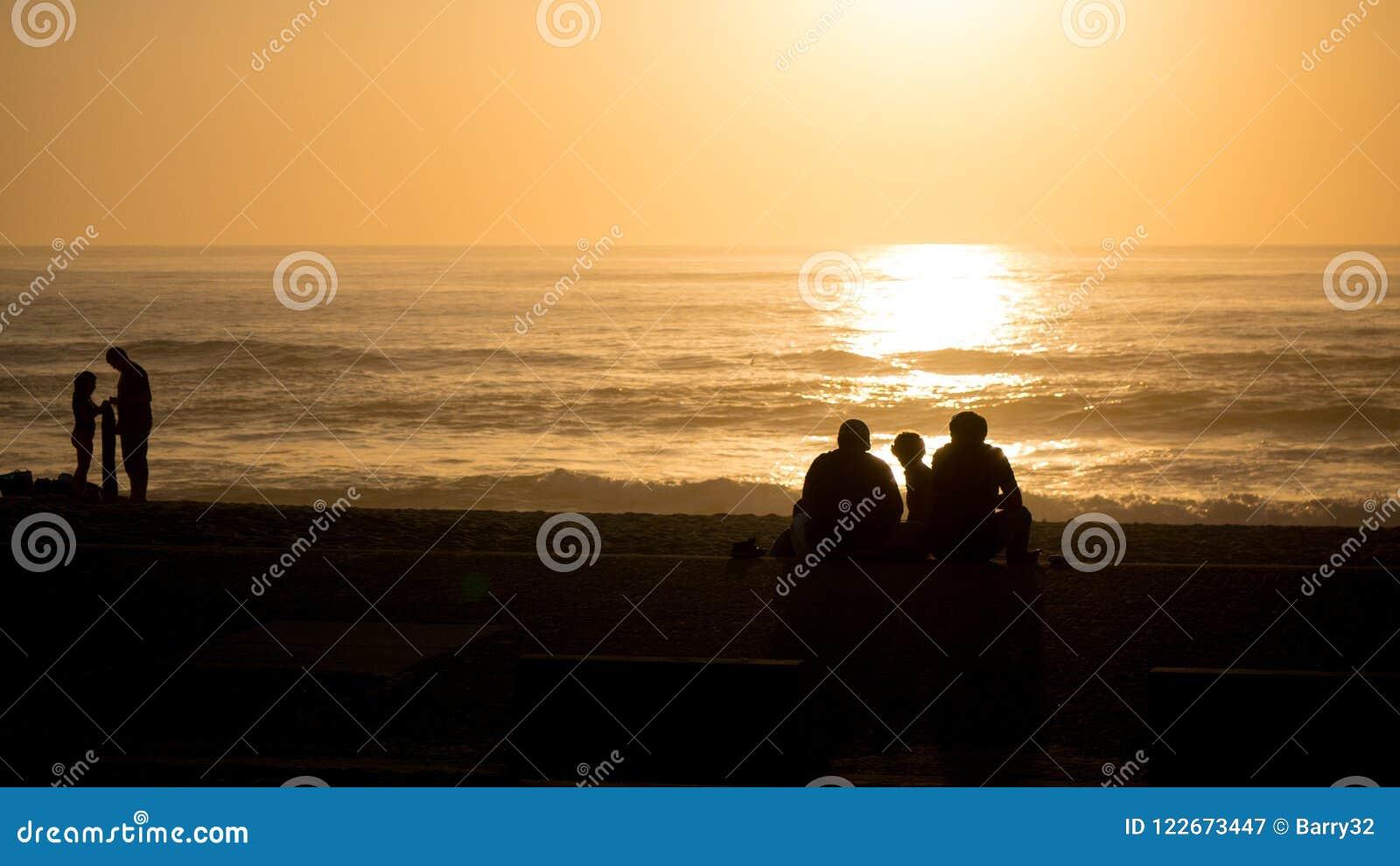 Por do sol vívido bonito da praia com os povos mostrados em silhueta sobre Oceano Atlântico em Vila do Conde, Porto, Portugal