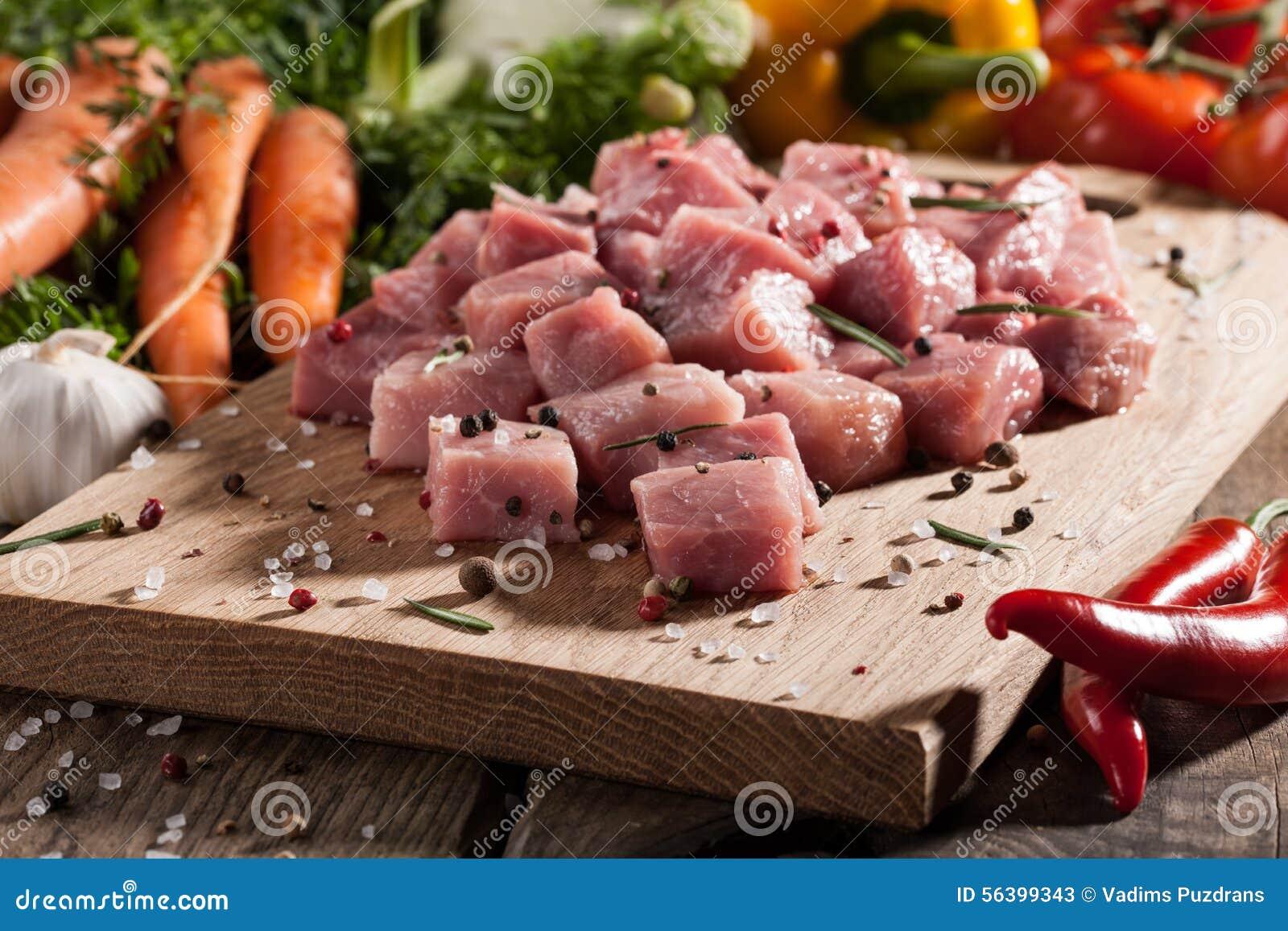 Porc cru sur la planche à découper et les légumes frais