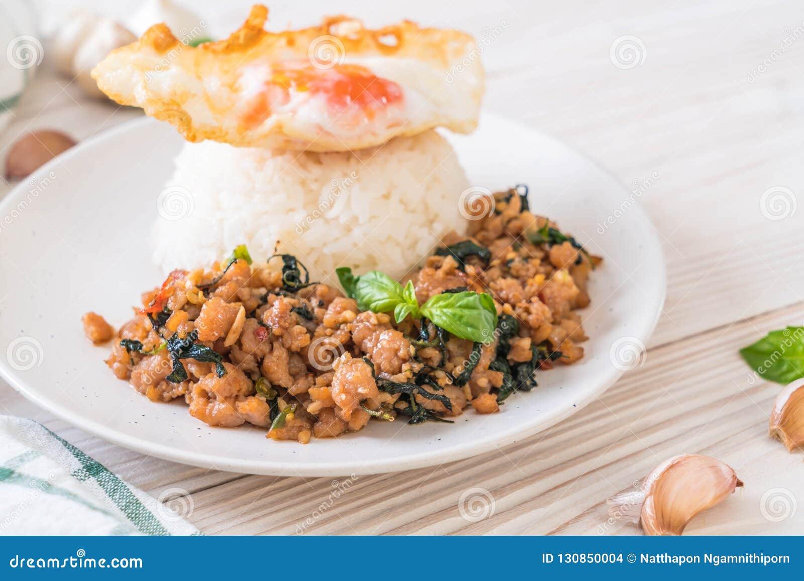 Porc fait sauter à feu vif avec le basilic sur le riz et l oeuf au plat