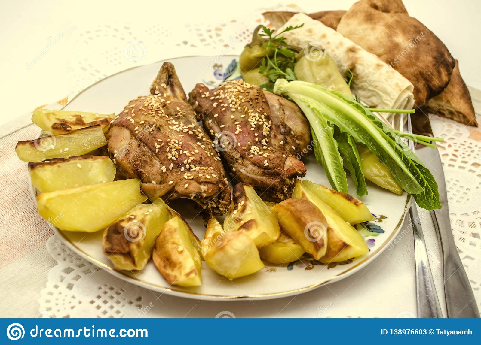 Porcelain plate with fried pieces of chicken and potatoes, sprinkled with white sesame and black pepper, next to the salad and pe. A large plate with fried stock photos