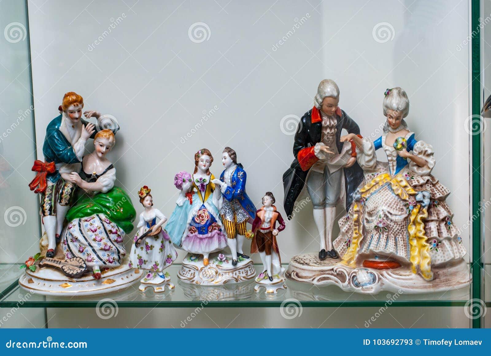 Assortment Of Rare Porcelain Figurines On Glass Shelf Stock Image