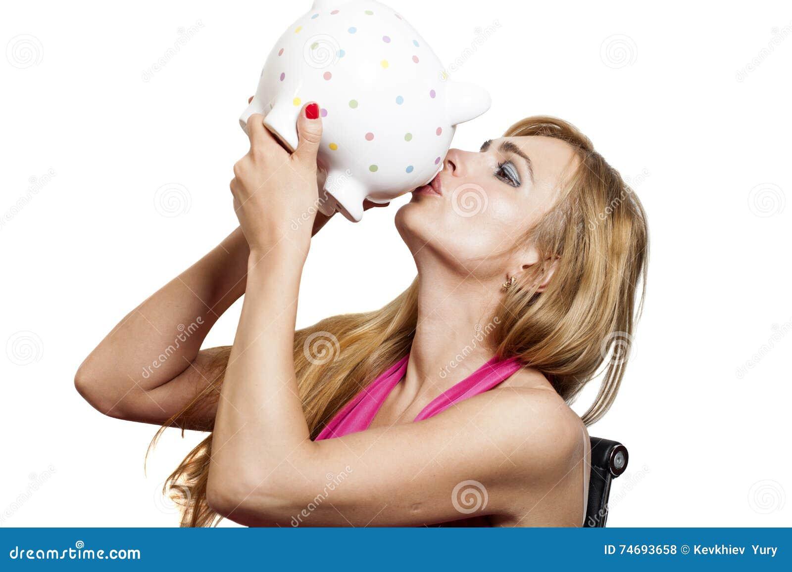 Porcellino salvadanaio baciante della bella giovane donna isolato su bianco