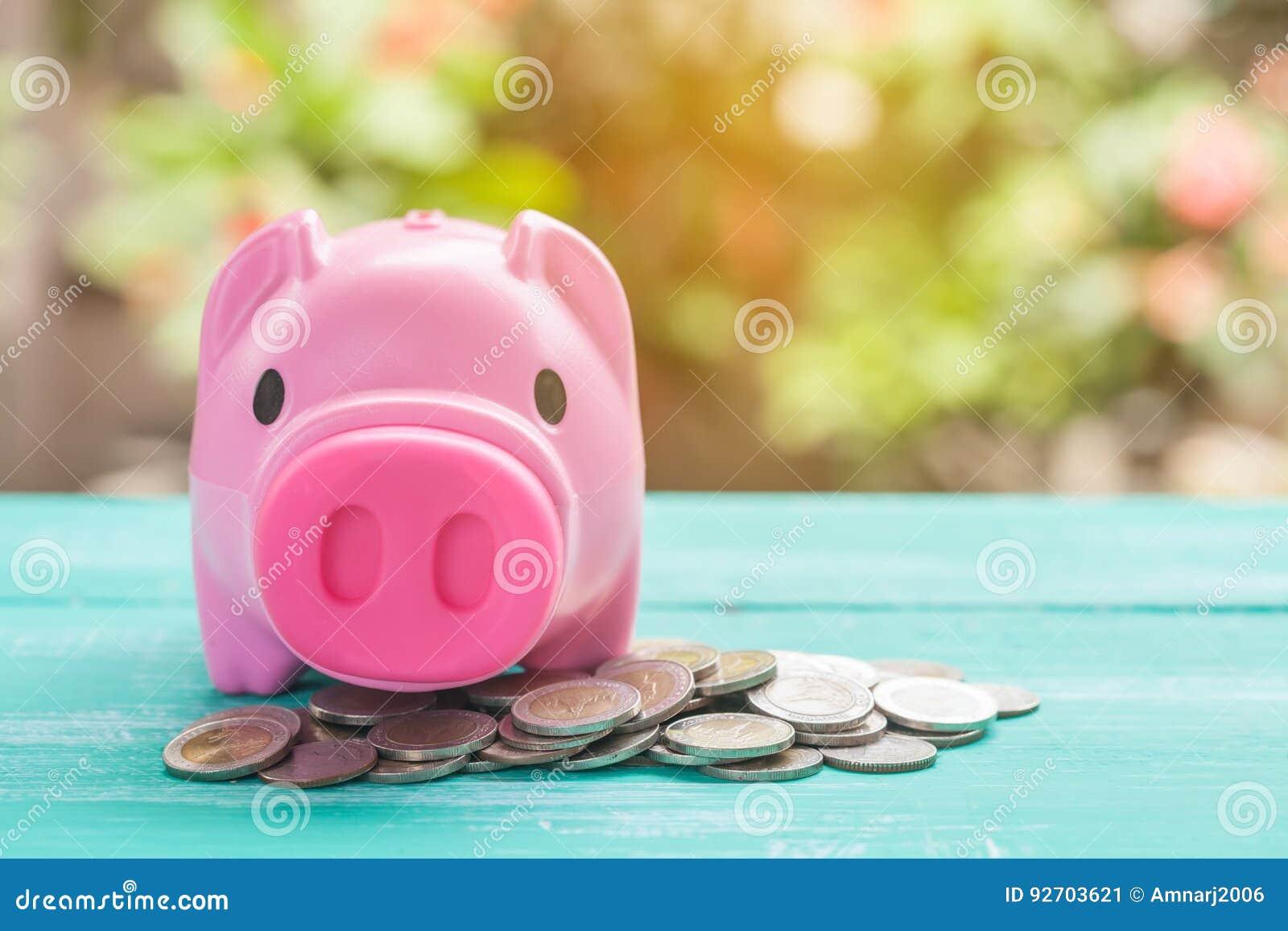 Porcellino salvadanaio rosa sopra la pila delle monete, soldi di risparmio