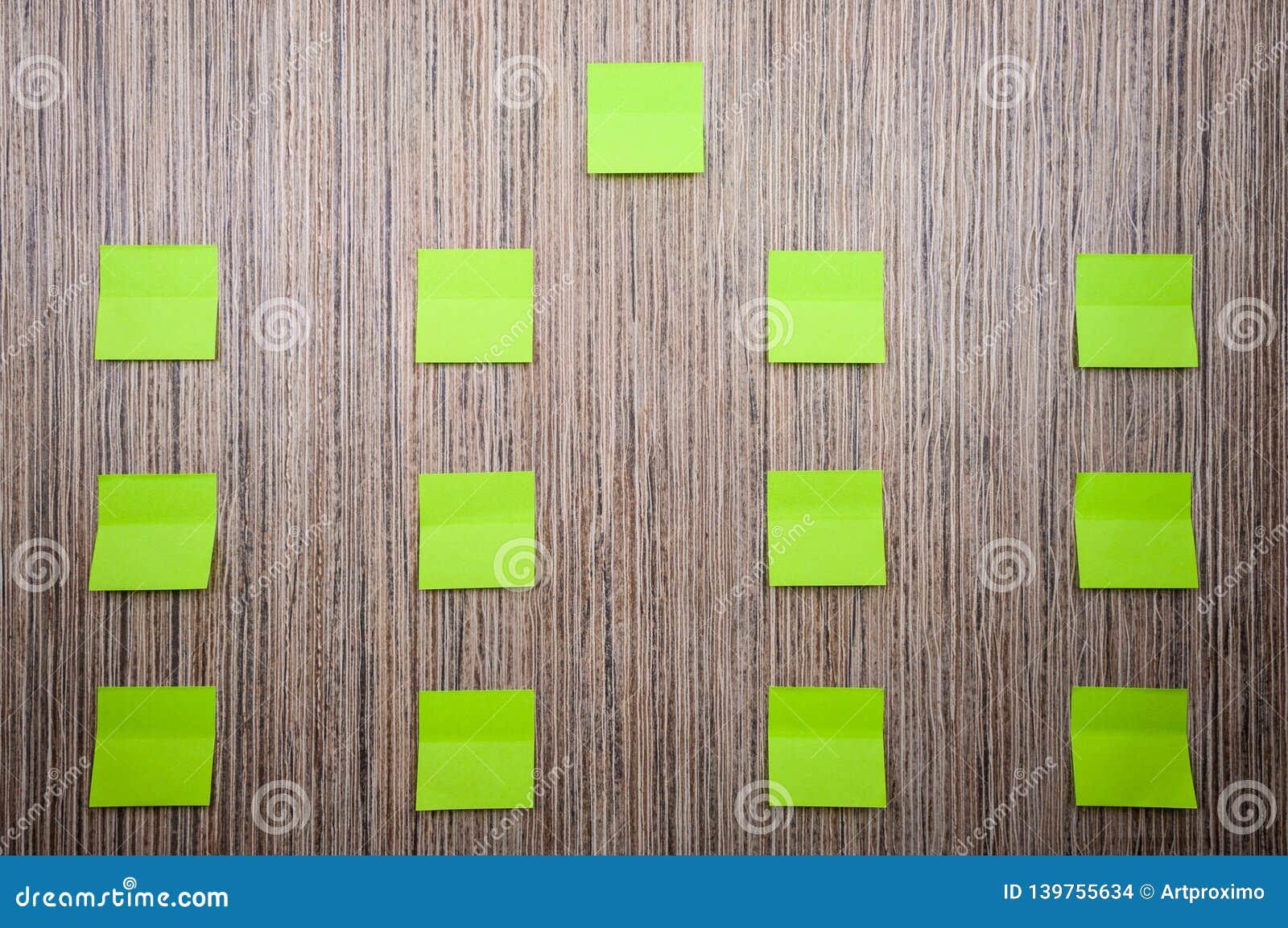 Porción de etiquetas engomadas verdes para las notas sobre un fondo de madera Maqueta para el diseñador