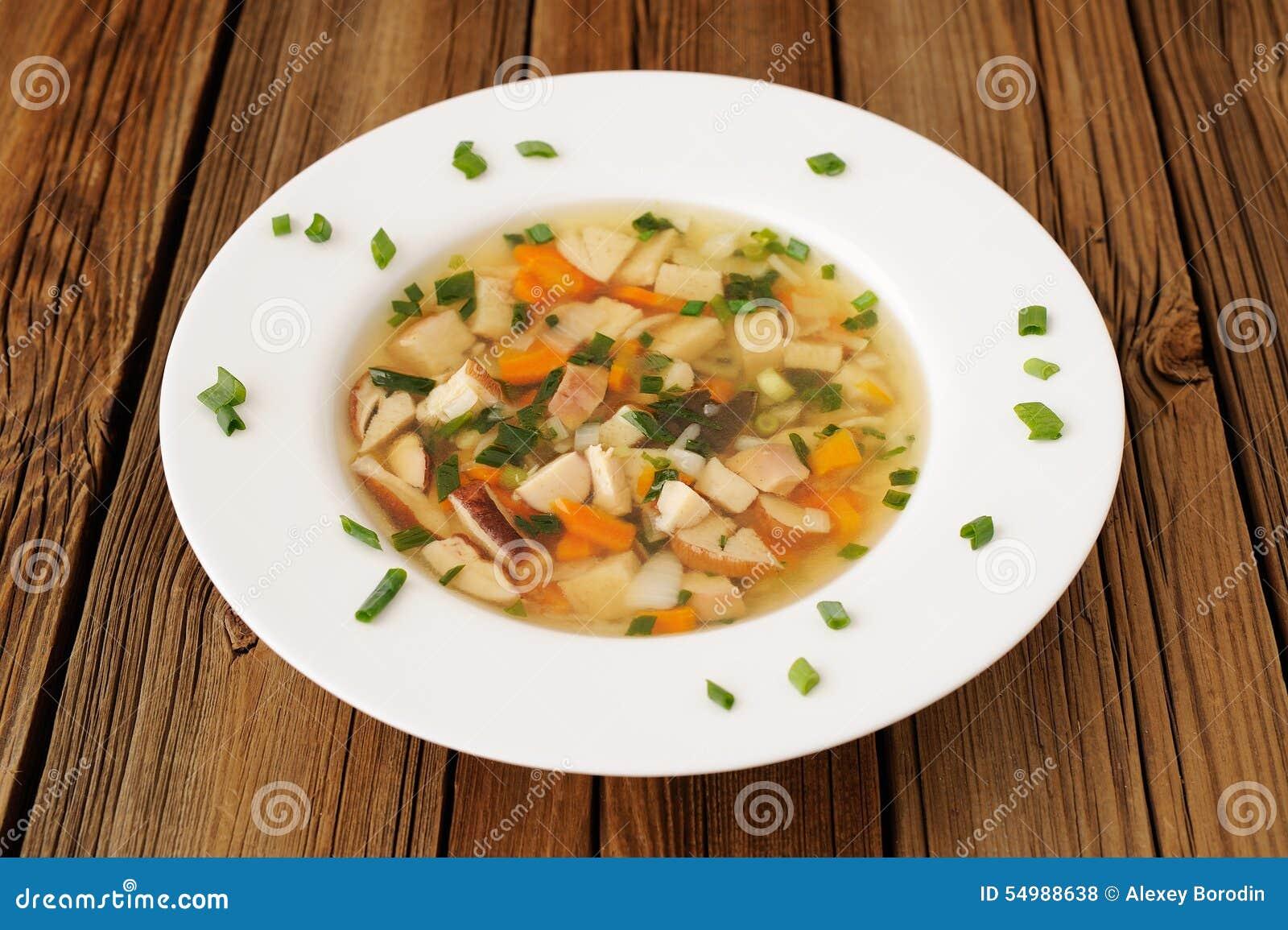 Porcini champinjonsoppa med salladslök i den vita plattan på trälodisar