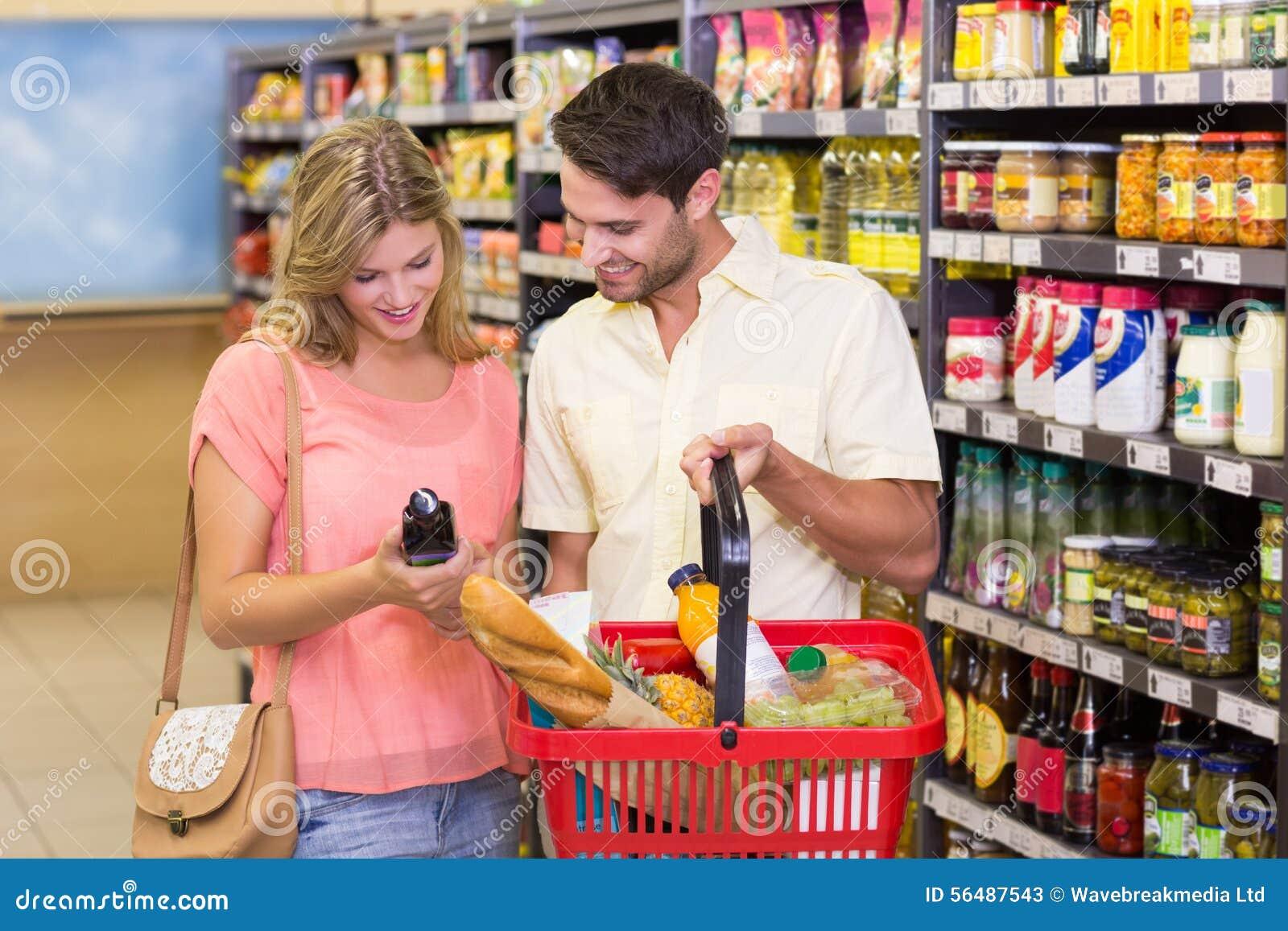 Porducts de achat de sourire de nourriture de couples lumineux avec le panier à provisions