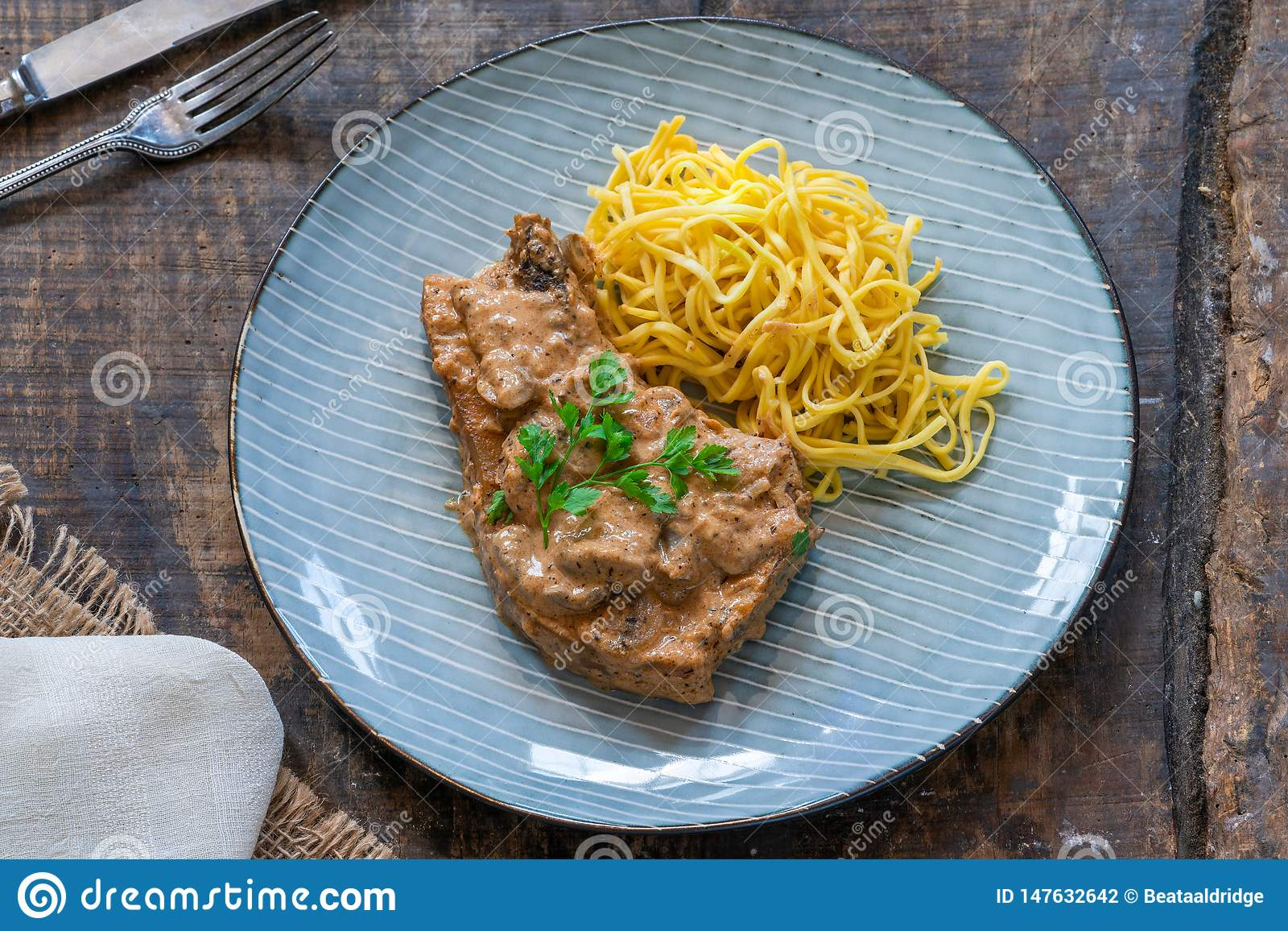 Pork chops in creamy cajun sauce with button mushrooms and egg noodles