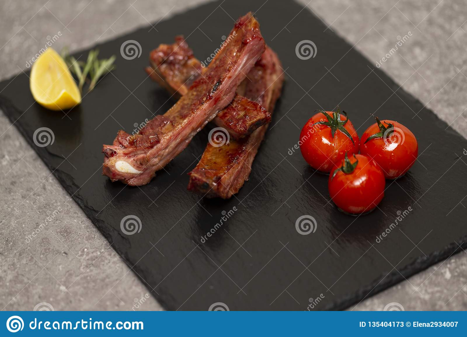 Pork ribs in barbecue sauce and honey roasted tomatoes on a black slate dish.