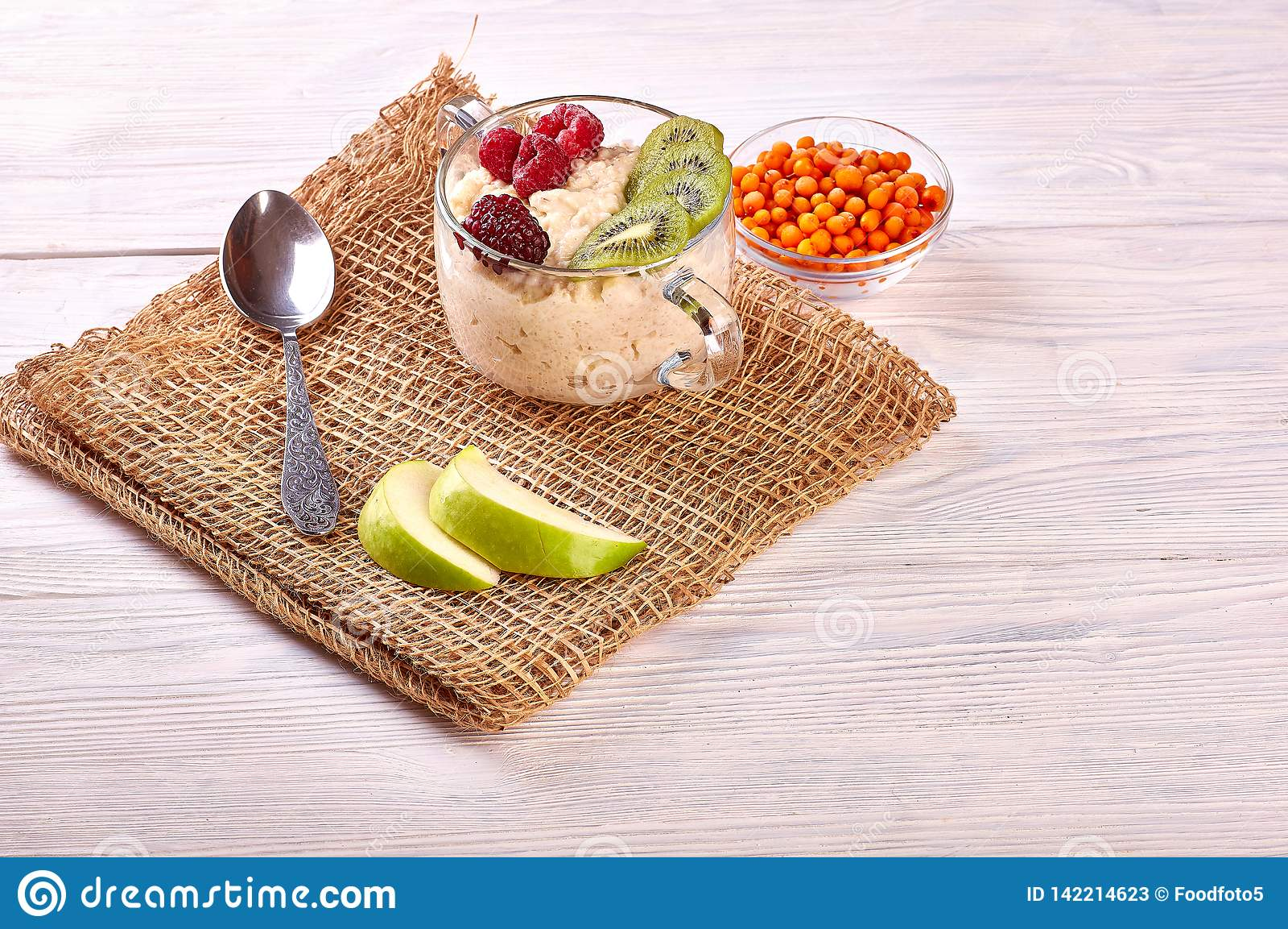 Porridge with fruit on wooden background