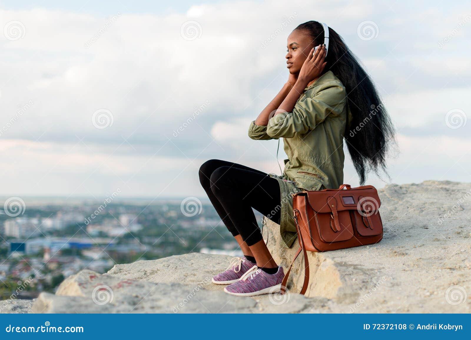 有智能手机和耳机的听到在蓝色多云的音乐的华美的非裔美国人的行家妇女Porrtrait
