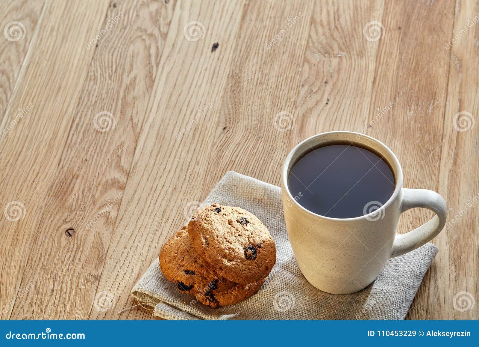 Porslintekopp med kakor för chokladchiper på bomullsservetten på en lantlig träbakgrund, bästa sikt