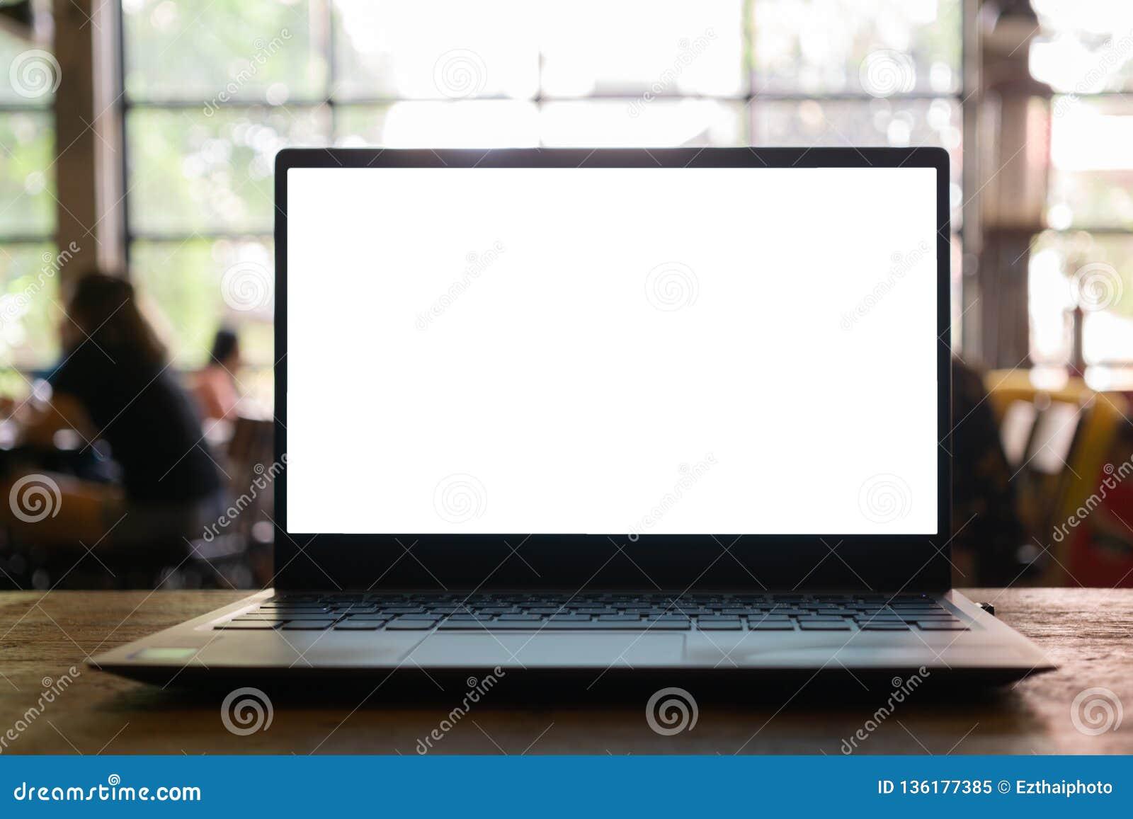 Portátil com a tela vazia na tabela com fundo borrado da cafetaria
