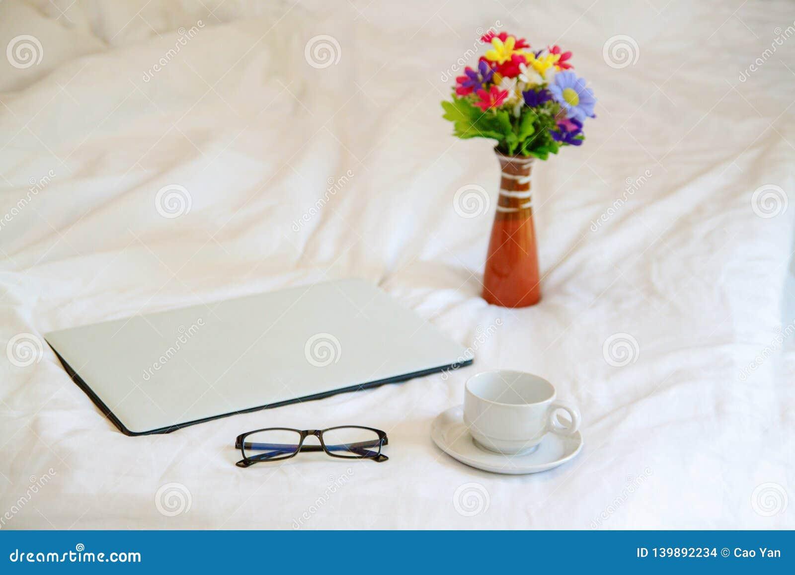 Portátil com vidros e copo de café no fundo branco