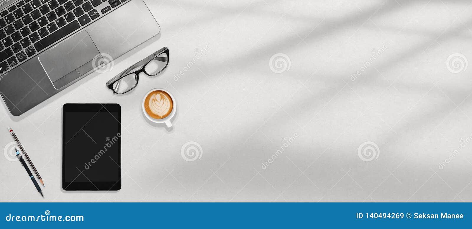 Portátil do espaço de trabalho do escritório, tabuleta, vidros do olho e café flatlay no desktop branco