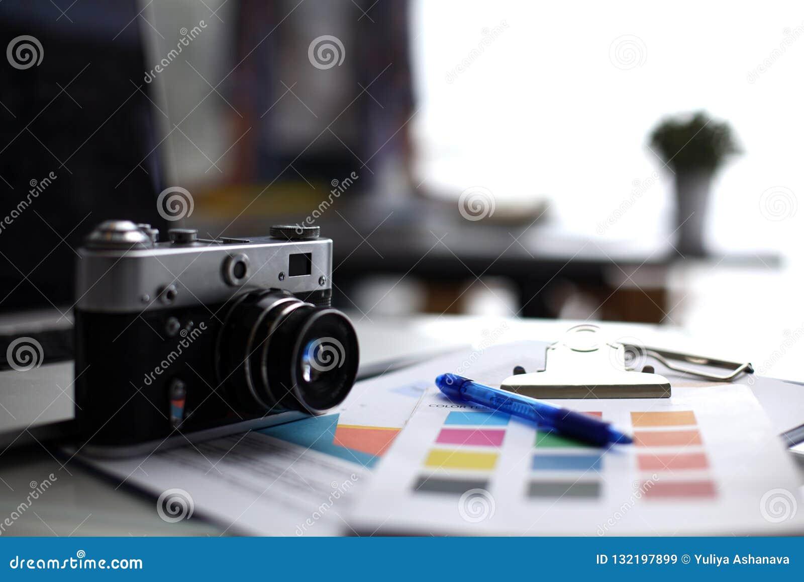 Portátil e câmera na mesa, dois empresários que estão no fundo